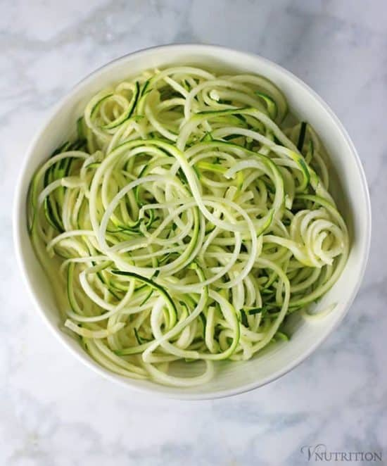 overhead shot of spiralized zucchini noodles in white bowl
