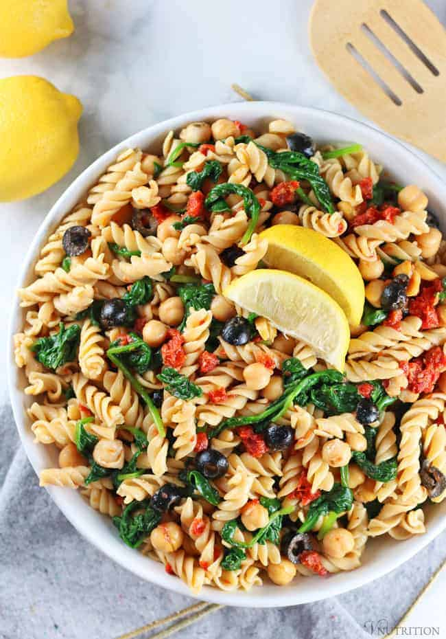 overhead shot of Vegan Pasta Salad in white bowl with grey napkin, lemons and wooden tongs