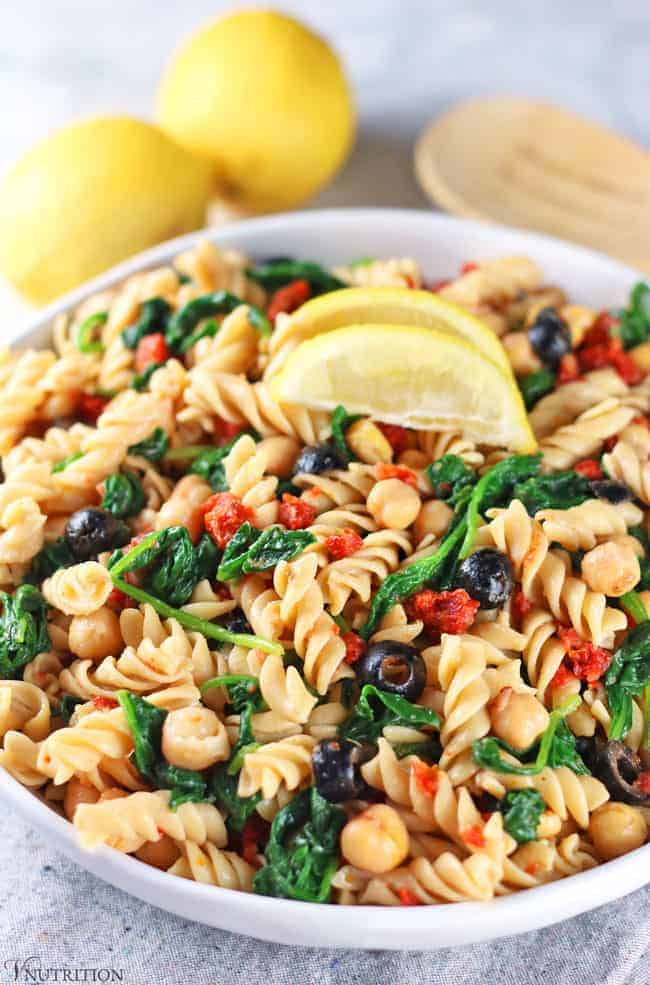 Vegan Pasta Salad with lemons and tongs in background