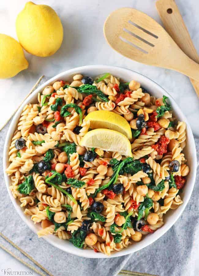 Easy Vegan Pasta Salad with lemons, tongs, and grey napkin