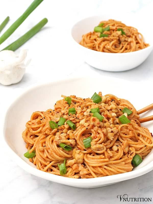 Spicy Sesame Noodles in bowl with garlic, scallion and smaller bowl in background
