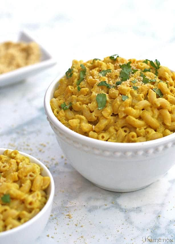 large bowl of cashew mac and cheese with smaller bowl in foreground and Parmesan in background