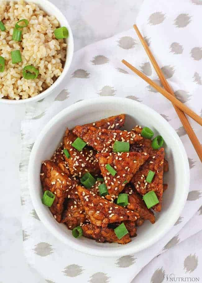 teriyaki tempeh with napkin, chopsticks and bowl of brown rice
