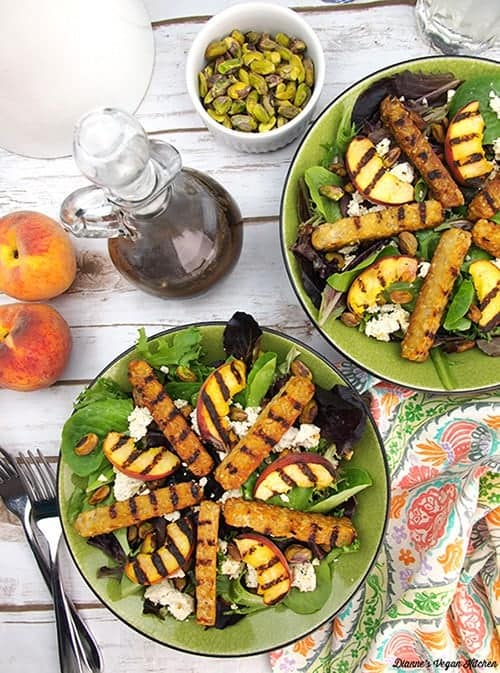 overhead shot of grilled tempeh salad including salad dressing, pistachios, peaches and utensils for vegan sides for grilling