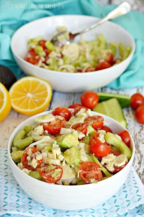 hearts of palm salad in foreground with bowl, lemons, tomatoes and cucumber in background for vegan sides for grilling