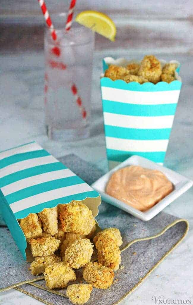 Air Fryer breaded tofu nuggets in a white and turquoise striped cardboard snack container with a side of sriracha mayonnaise