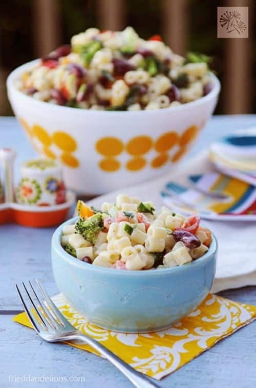 vegan macaroni salad with fork in forefront and large bowl of salad in background for vegan sides for grilling