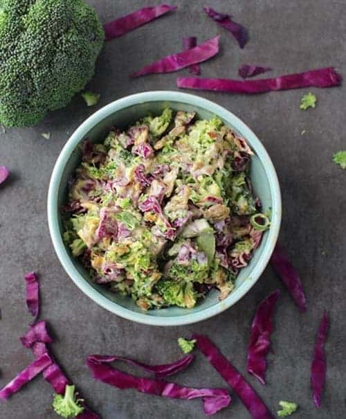 overhead shot of easy vegan broccoli slaw with broccoli and cabbage surrounding it for vegan sides for grilling