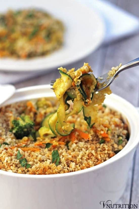 forkful of zucchini carrot vegetable casserole atop a full casserole dish