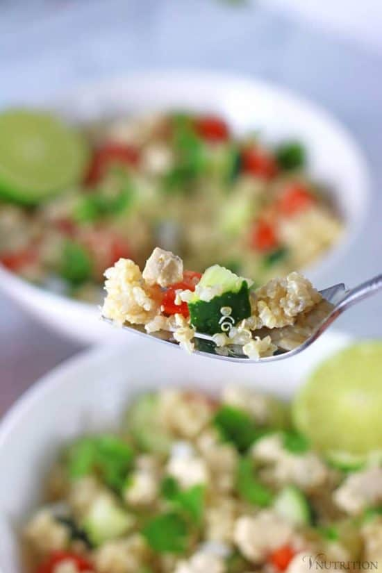 fork full of Mediterranean Quinoa Salad with bowls in background