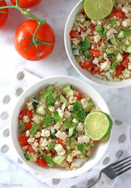 overhead shot of 2 bowls of Mediterranean Quinoa Salad with fork, napkin, and tomatoes