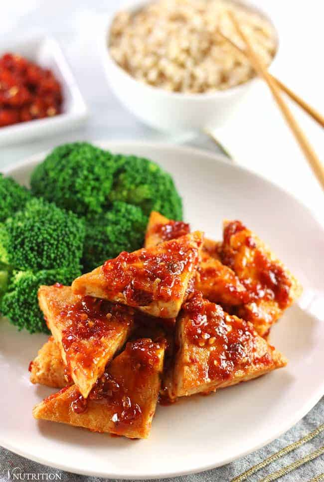 garlic chili tofu on white plate with broccoli and brown rice with chopsticks and chili sauce in background