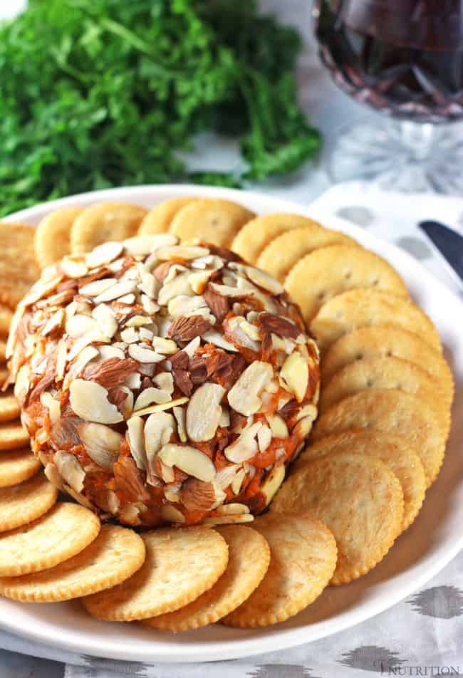 vegan port wine cheese covered in almonds with crackers around the cheese and greens and port wine in glass in the background