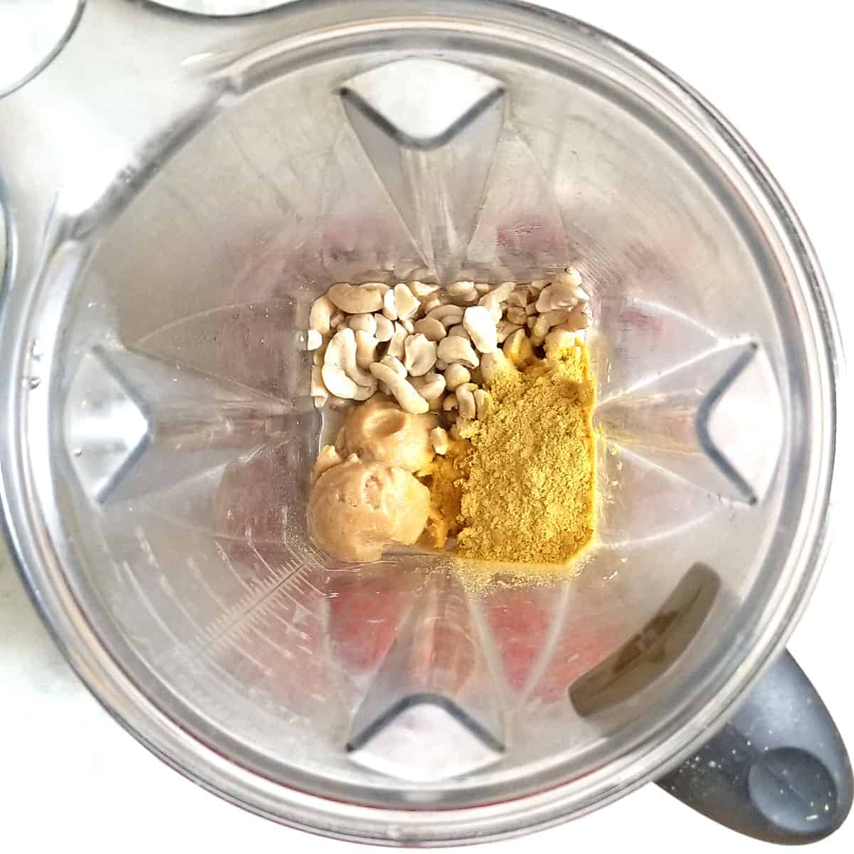 nutritional yeast, soaked cashews and other ingredients in blender pitcher to be blended into cashew cheese sauce for vegan mac and cheese