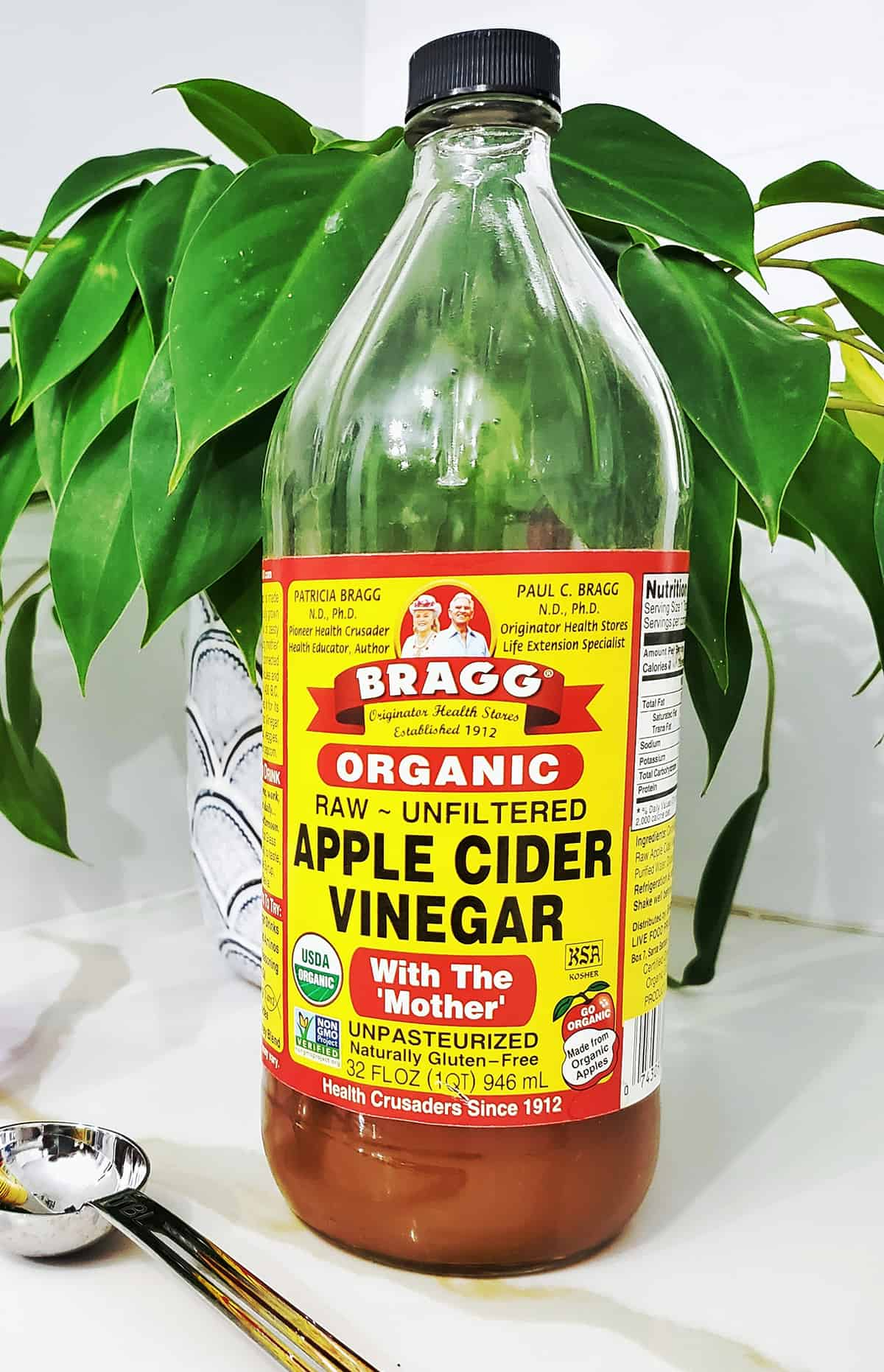 bottle of apple cider vinegar with a plan and measuring spooon