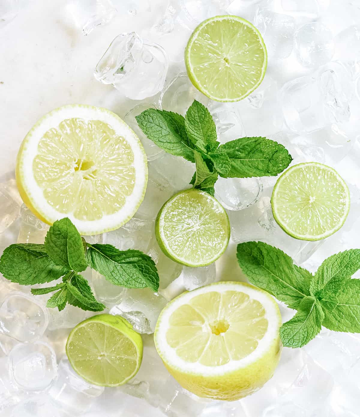 lemons and limes on a white table with ice and mint