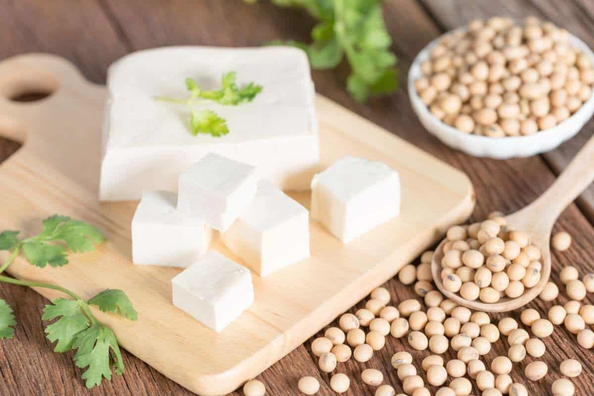 block of tofu on a wooden cutting board with a few cubes that have been cut, some cilantro leaves as garnish, and a scattering of soybeans