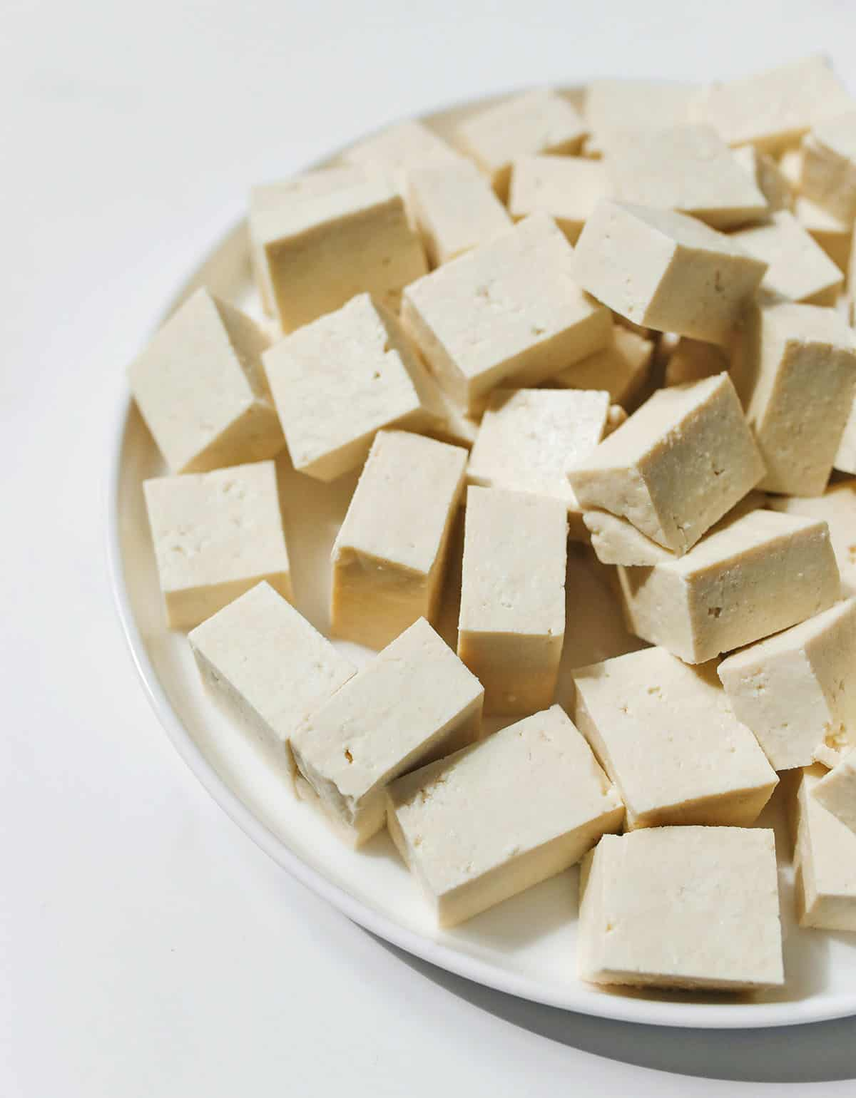 cubes of tofu on a white plate on a white background