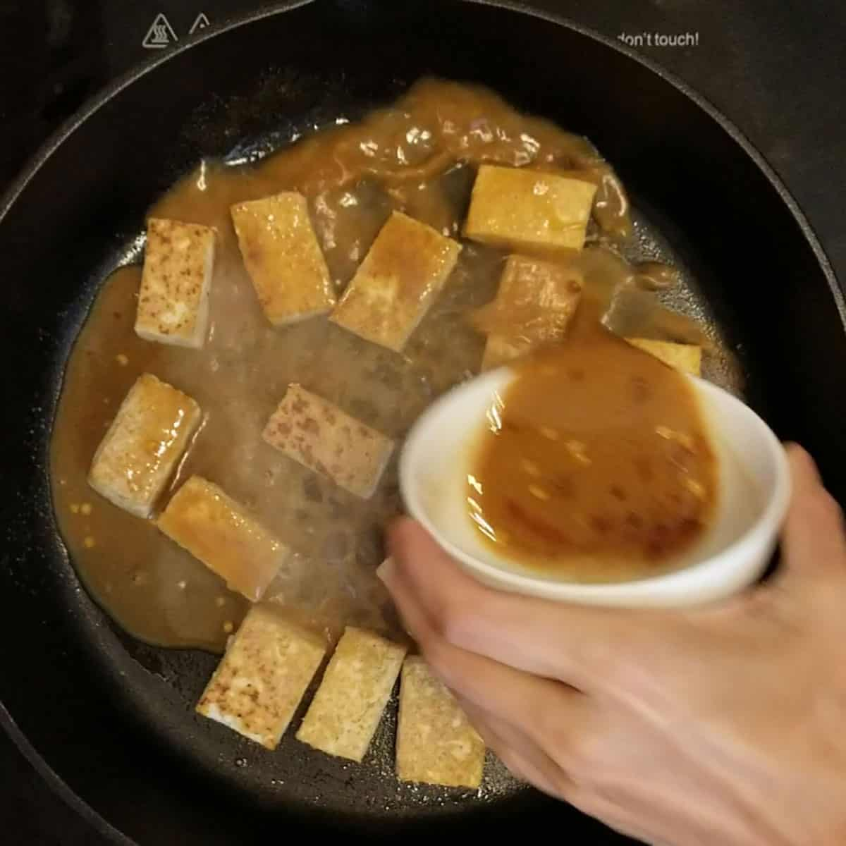 pouring sauce on fried tofu