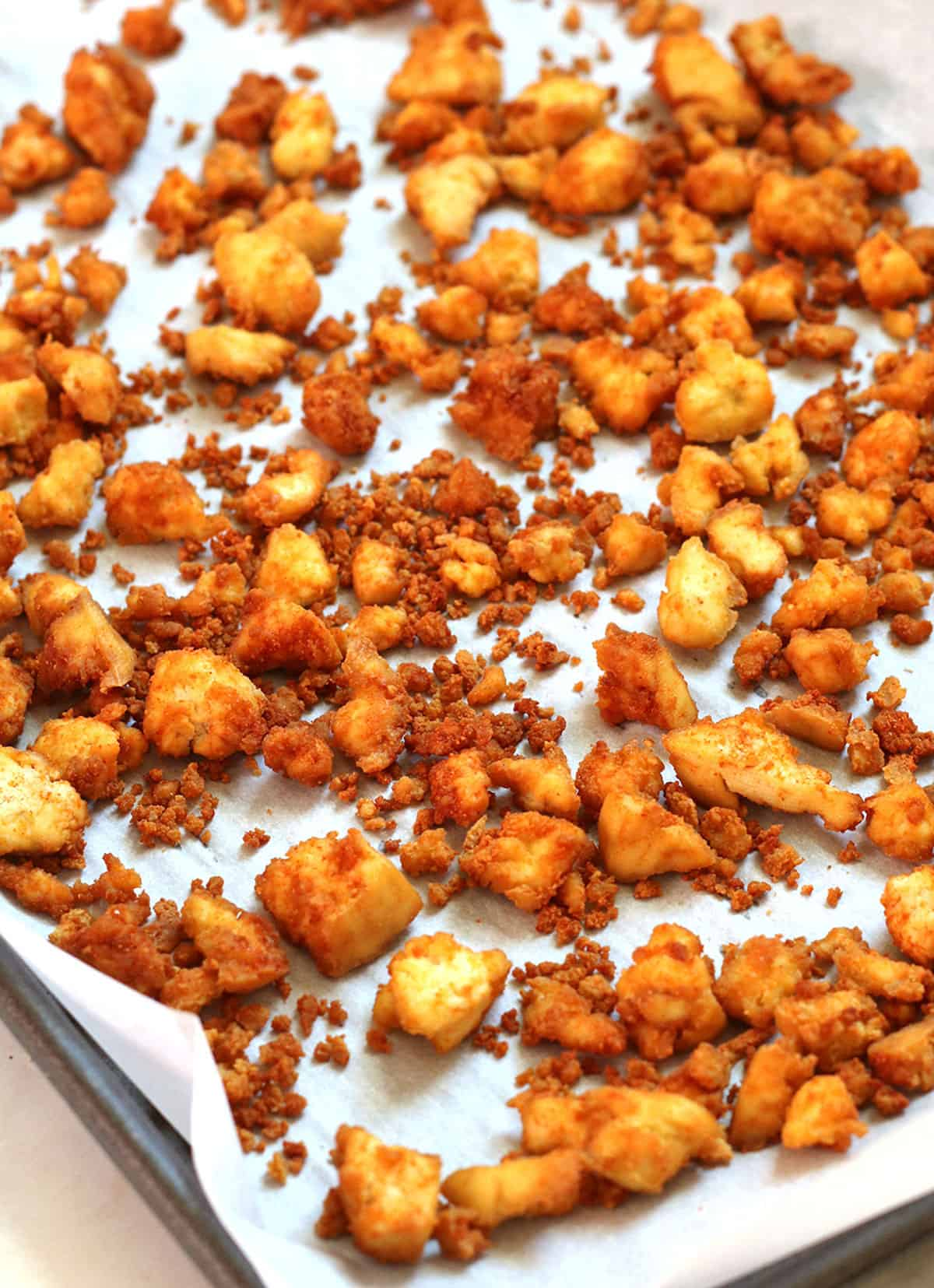 tofu crumbles on a sheet pan with parchment paper