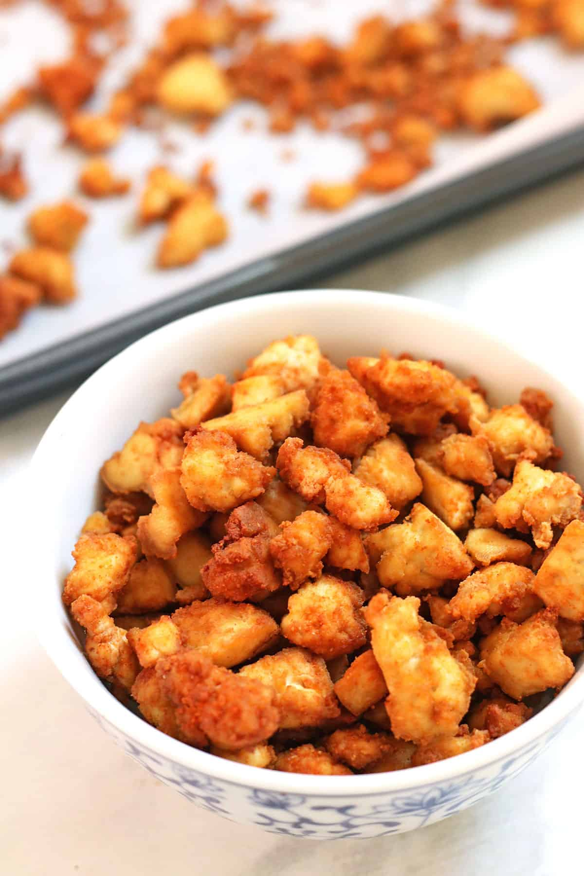 tofu crumbles in a bowl and on sheet pan