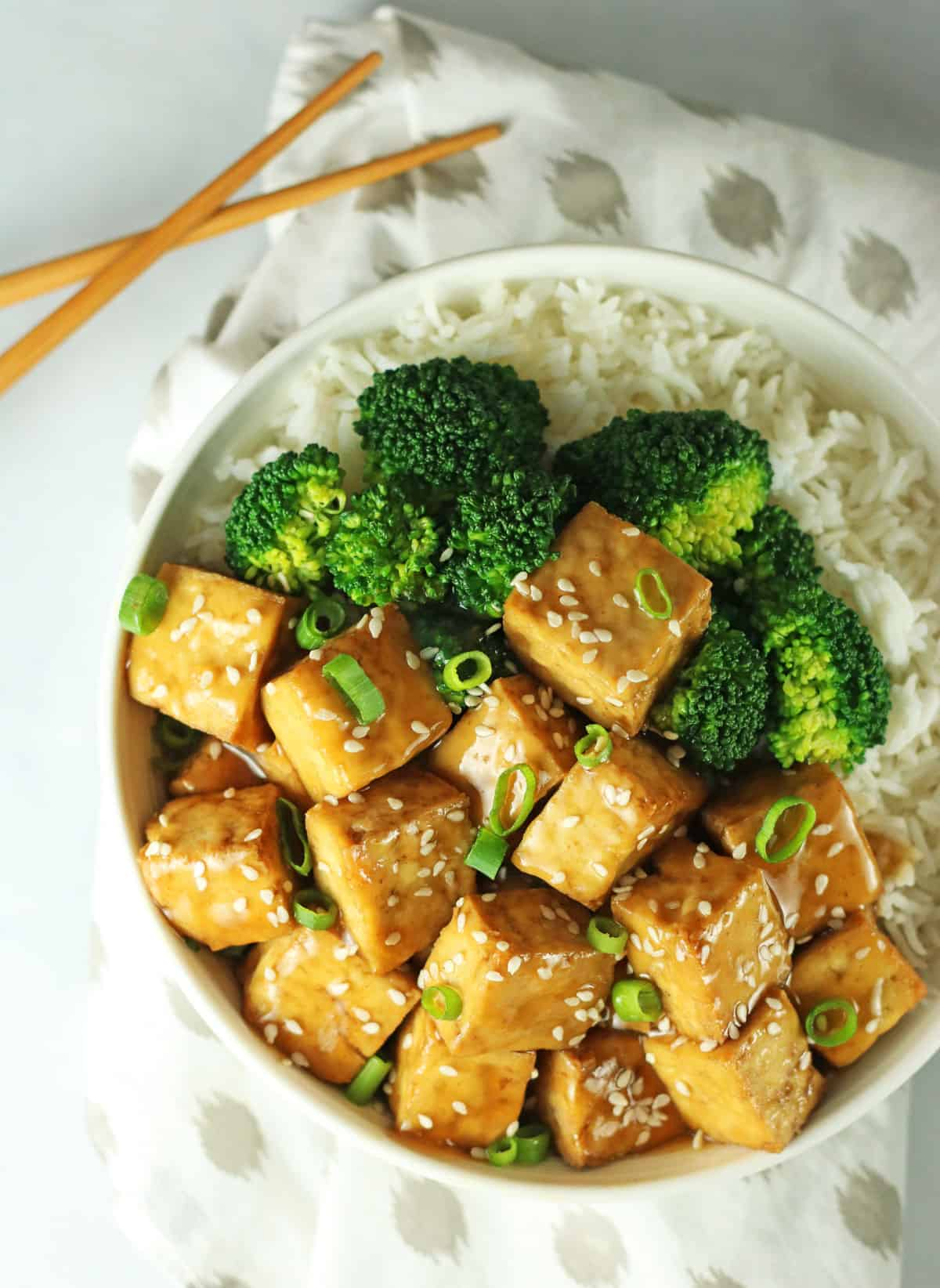 close up shot of a white bowl filled with sticky rice, steamed broccoli and vegan teriyaki tofu cubes