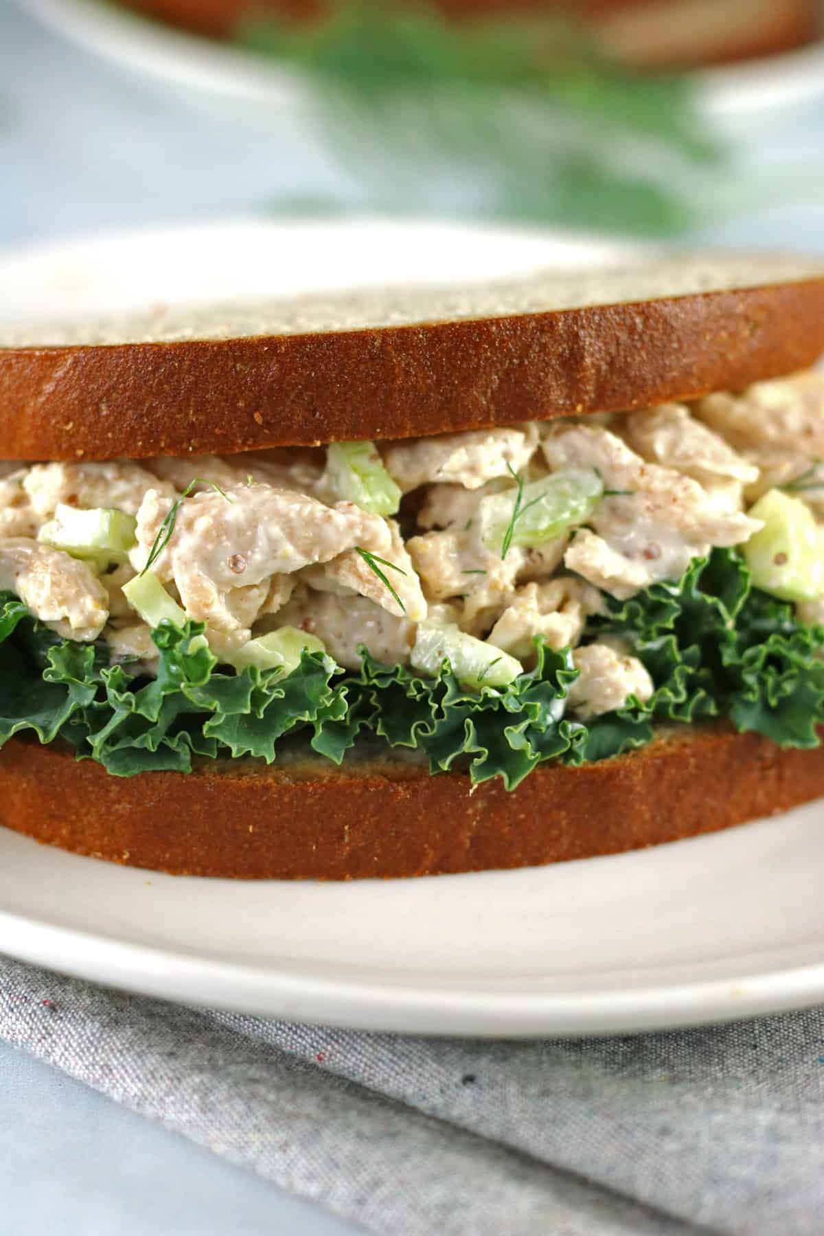 vegan chicken salad in a sandwich with lettuce on a white plate and gray napkin