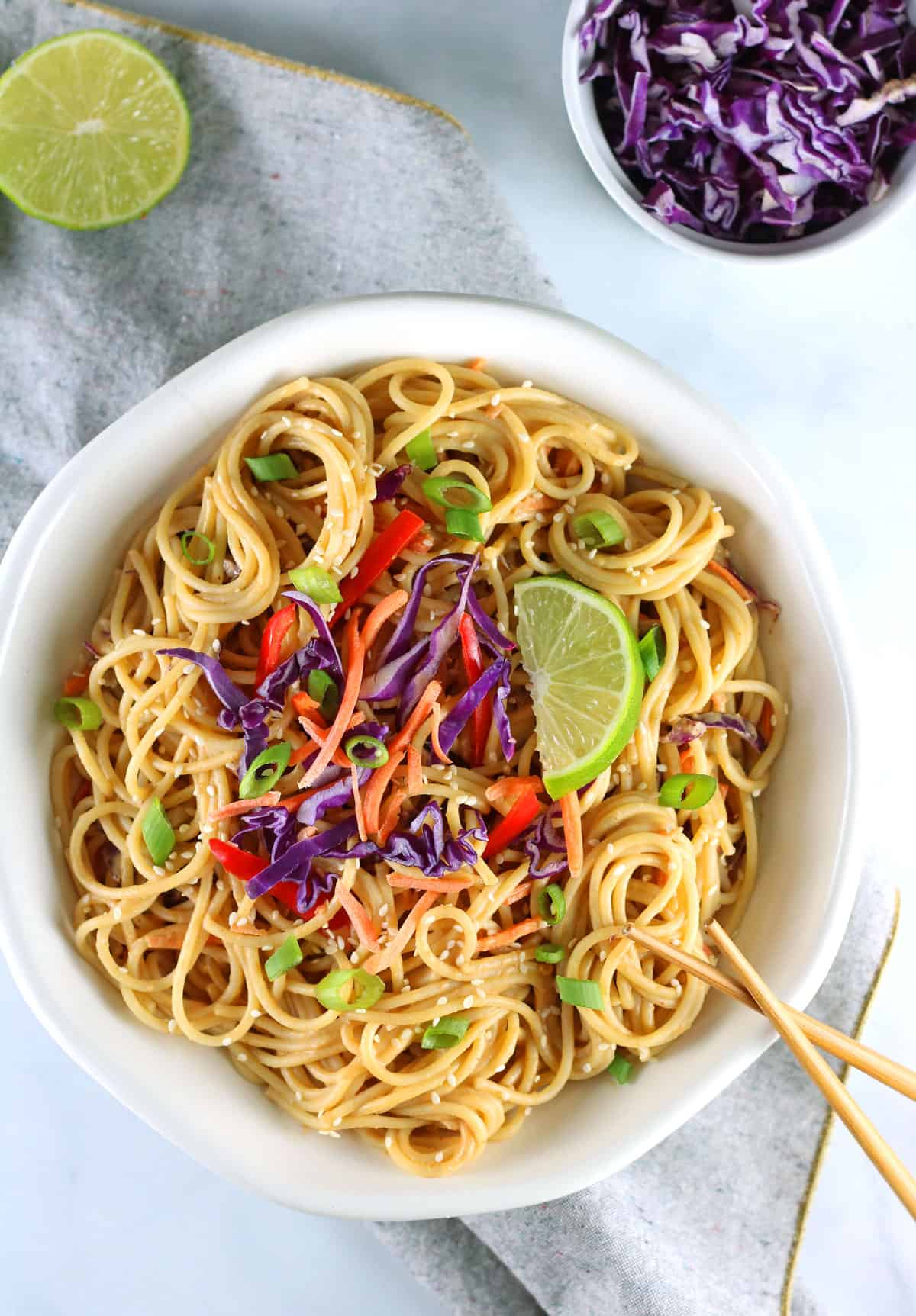 vegan peanut noodles overhead shot with lime, cabbage and chopsticks