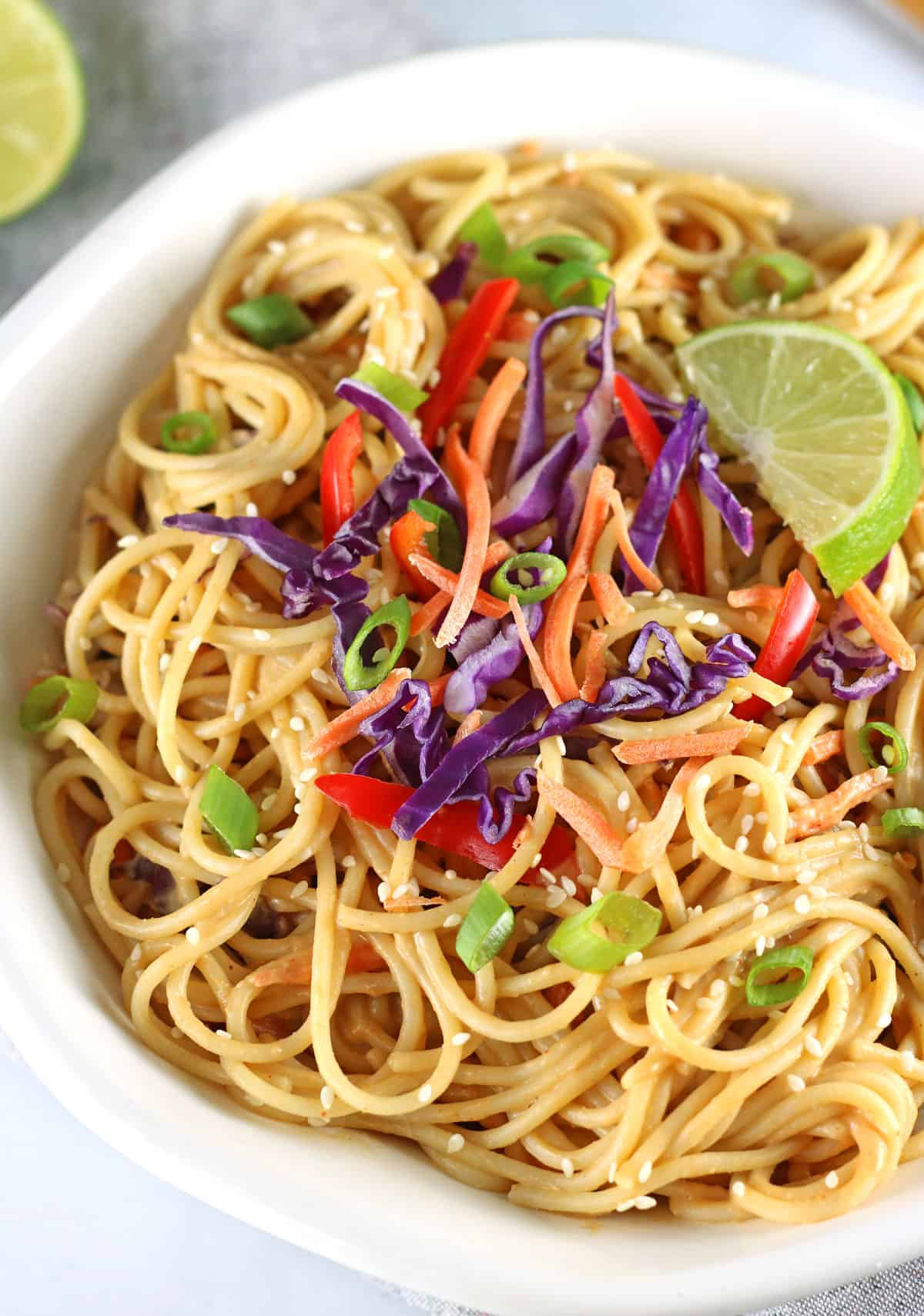 closeup of vegan peanut noodles with veggies and a lime wedge