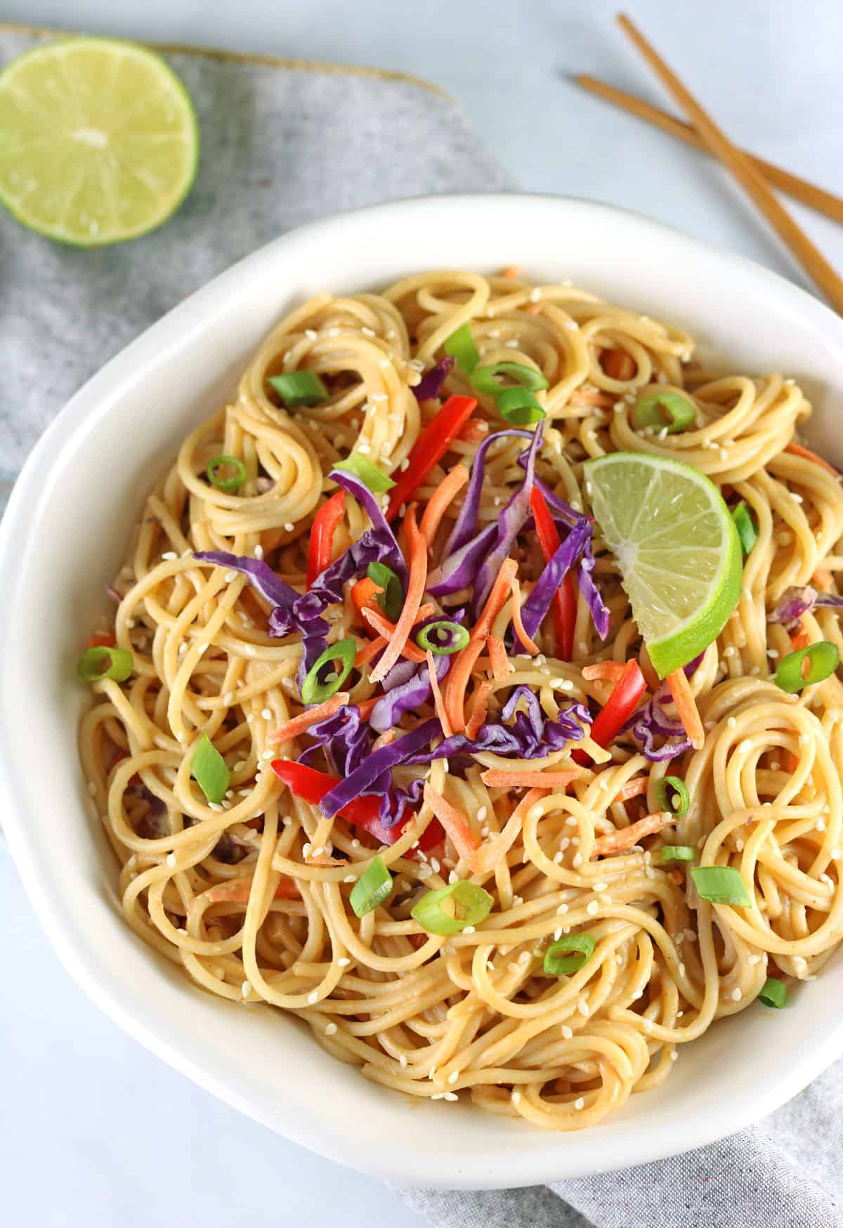peanut noodles with lime and chopsticks on grey napkin