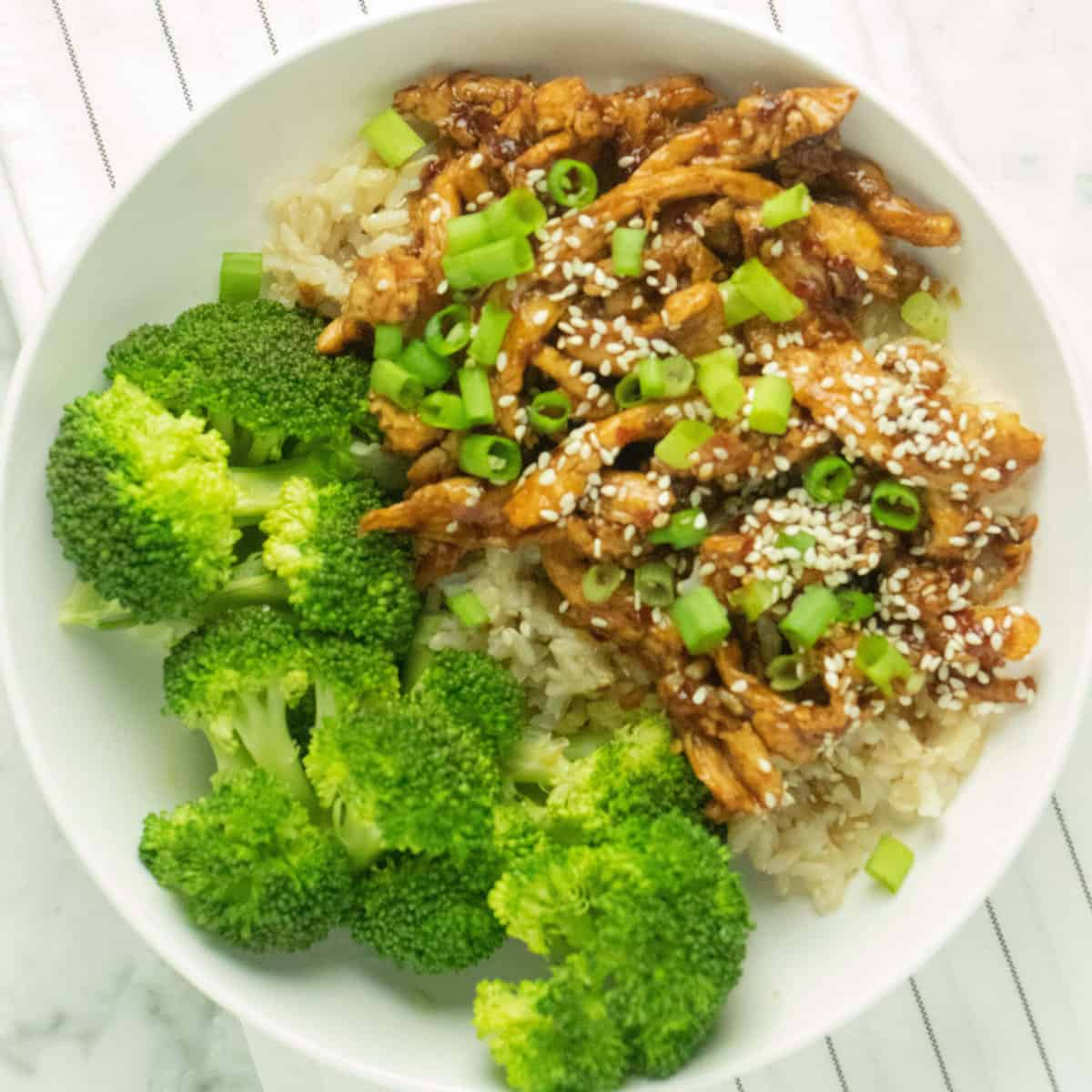overhead shot of mongolian soy curls on a bed of brown rice with a side of steamed broccoli on a round white plate