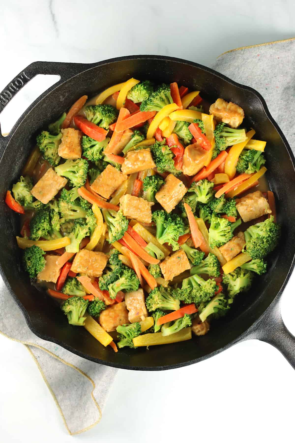 tempeh stir fry in pan with gray napkin underneath