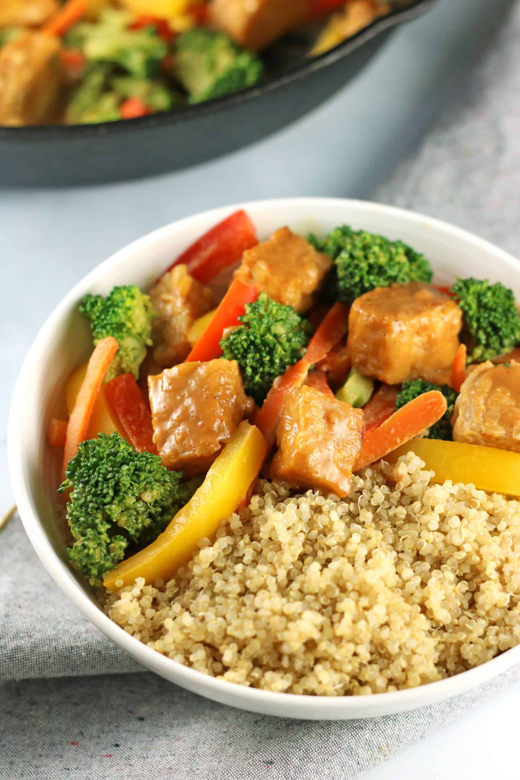 tempeh stir fry in white bowl with quinoa