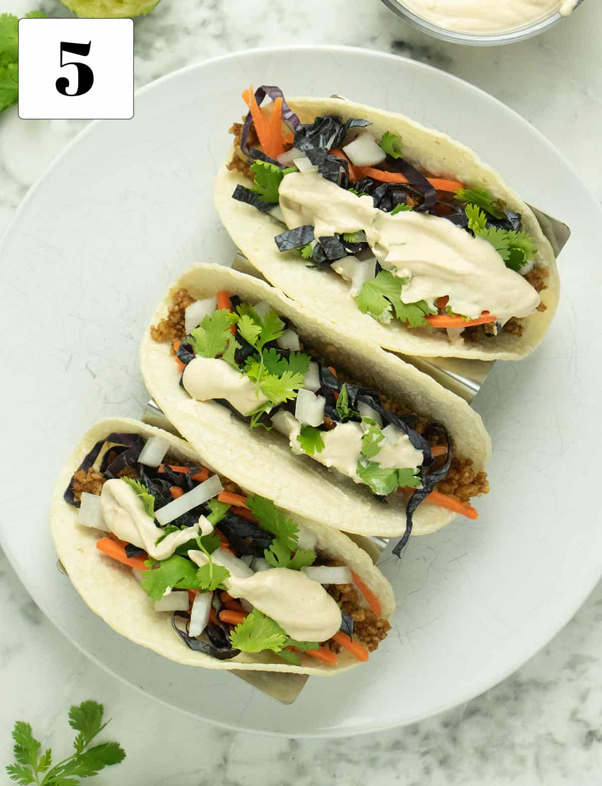 overhead of 3  tacos with toppings and cashew lime cream