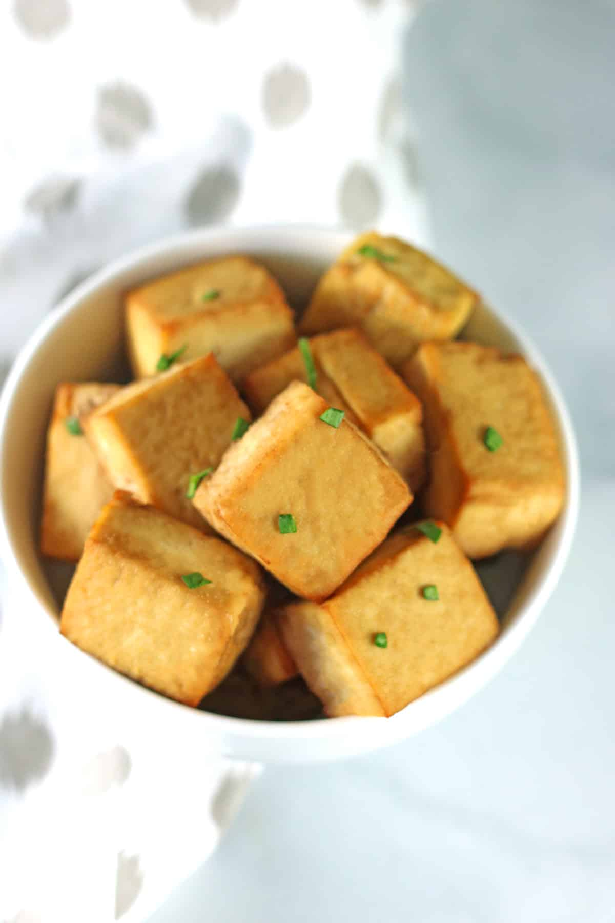 baked tofu in white bowl with white and gray napkin