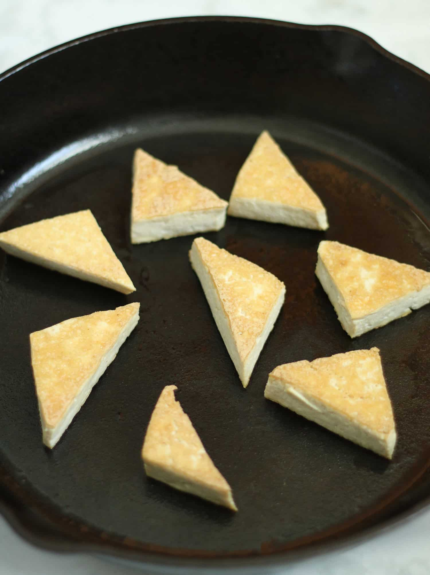 tofu triangles frying in cast iron skillet