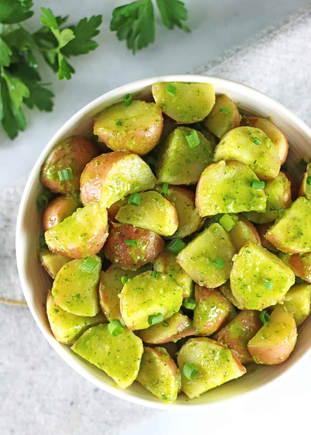 overhead of herbed potato salad in white bowl with fresh herbs