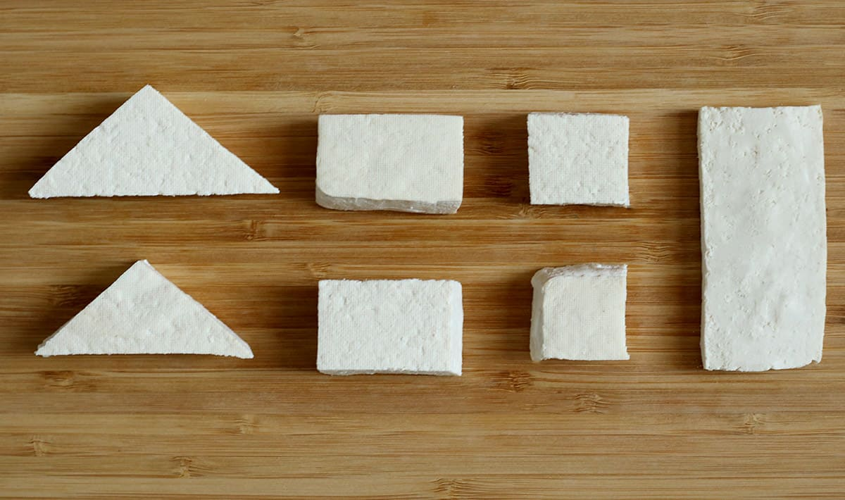 tofu cut into triangles, rectangles and squares on a wooden cutting board
