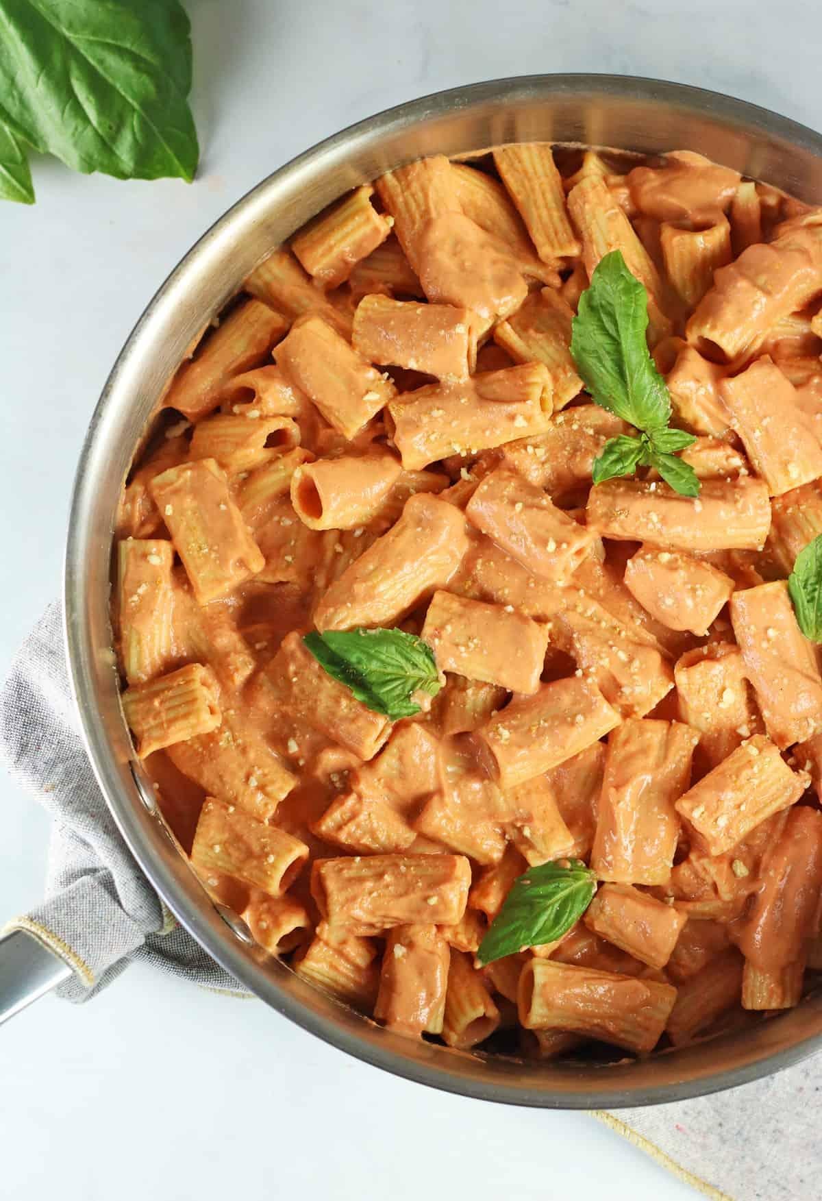 closeup of vegan vodka alla pasta in a pan with fresh basil
