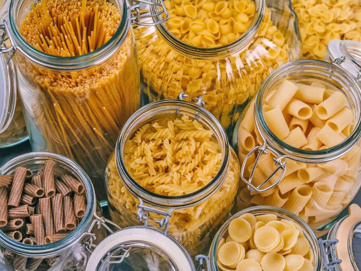 assorted dry pasta shapes in glass jars