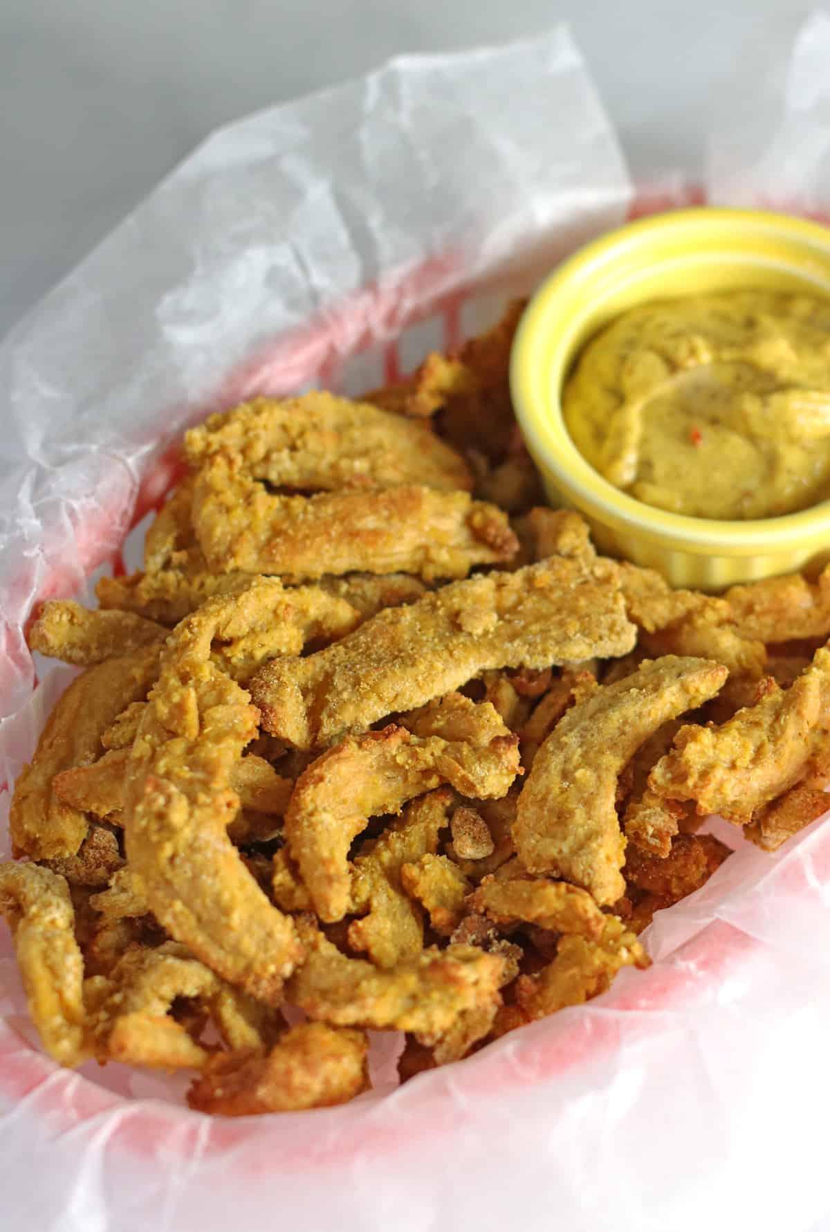vegan chicken in red basket with mustard dipping sauce