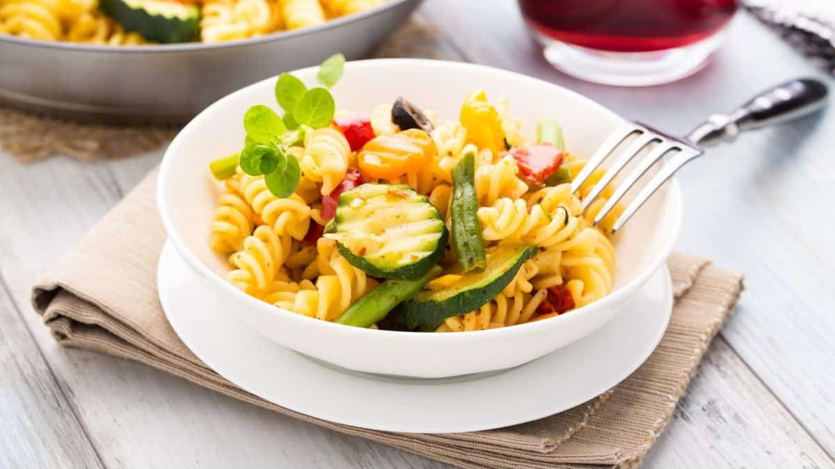 white plate and dish of pasta with veggies