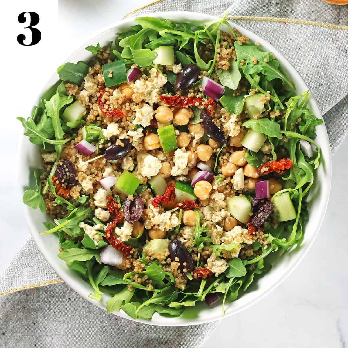 mixed mediterranean greek quinoa salad mixed with dressing