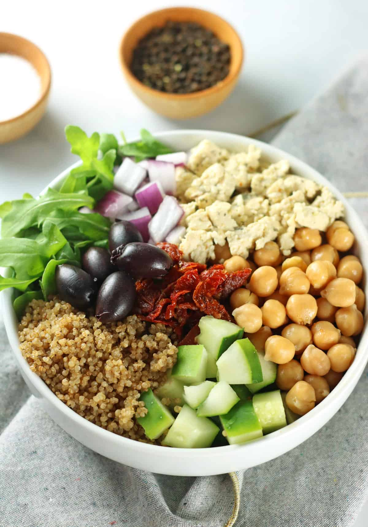Greek Quinoa salad in bowl with chickpeas, quinoa, cucumber, olives, onions and arugula.